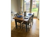 Solid oak dining room table with four chairs.
