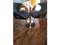 Modern style solid glass table and two comfortable stylish grey chairs