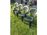 Four green plastic stackable garden chairs