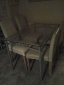 Glass dining table with 4 cream chairs.
