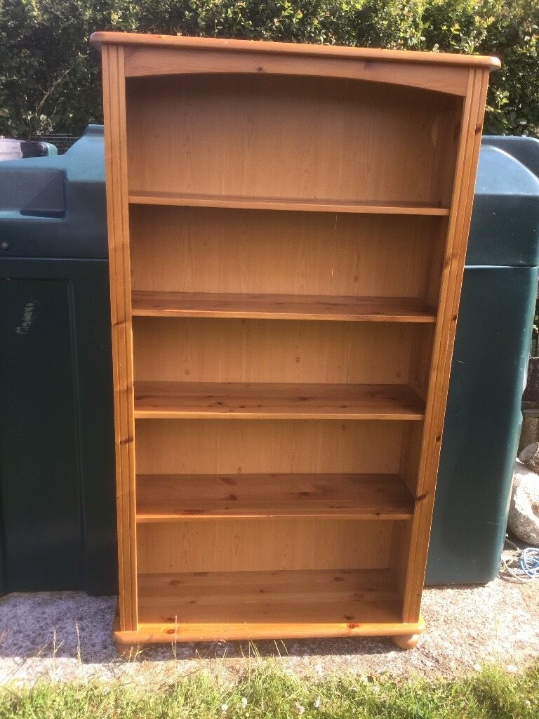 """Pine bookcasein Truro, CornwallGumtree - Pine bookcase with four adjustable shelves. Bookcase has rounded feet and is made from pine with a hardboard back panel. Could be used for books or to display other treasures. Measures 60"""" (153 cm) high x 10"""" (26cm) deep x 32"""" (82cm) wide. In good..."""