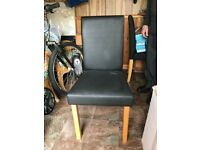 2 black leather chairs and small table.