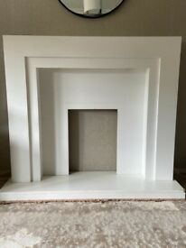 Contemporary white wood fire surround with down lights