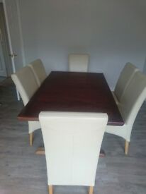 Rosewood dining table with 6 leather chairs and a rosewood sideboard
