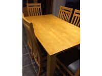 Maple coloured wooden table and six chairs with black faux leather seats. £120.00