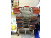 Wire shopping baskets on a wheeled and handled stand