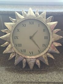 Gold sun shaped clock with Roman numeral numbers