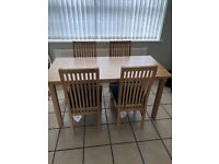 Oak dining table and 4 chairs. Table 150cm x 73cm. Chairs are oak and faux leather