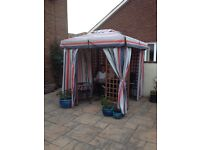 Marks & Spencer hard wooden gazebo with striped fabric drapes