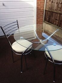 Glass and chrome Round table with four chairs