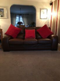 Pair of brown leather three seater sofas.