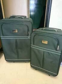 Two green suitcases (one medium, one small)