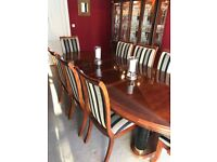 Stunning mahogany dining table with eight chairs and a glass-fronted cabinet.