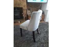 4 x luxury velvet dining chairs with chrome handles on the back.