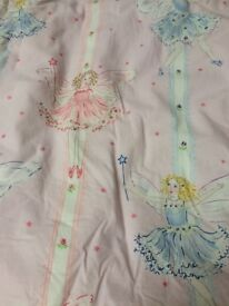 A pair of pink curtains with a fairy tale pattern