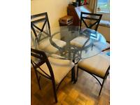 Glass top bronze stand dining table and matching cream chairs.
