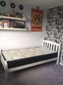 White wooden framed single bed with mattress