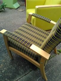 Upholstered green checked armchair with wooden arms. Very good condition, exdisplay.