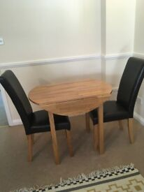 Solid oak wood table and four leather-cover chairs.