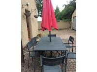 Patio table and 6 chairs with padded red cushions with matching parasol under 2 years old