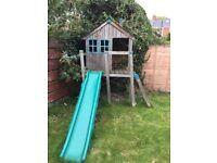 Children's outdoor wooden playhouse with plastic slide
