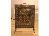 A simple Arts and Crafts brass and iron firescreen decorated with a Country scene .