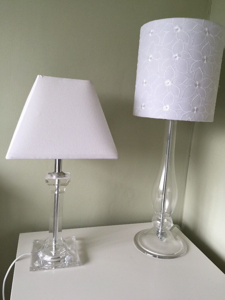 Two clear glass table lamps with white shades