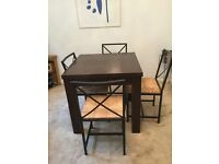Next Opus Mango extending dining table and four chairs.