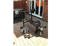Maximuscle weight bench with barbell weights and dumbbells.