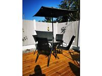 Black patio table, 4 chairs and parasol