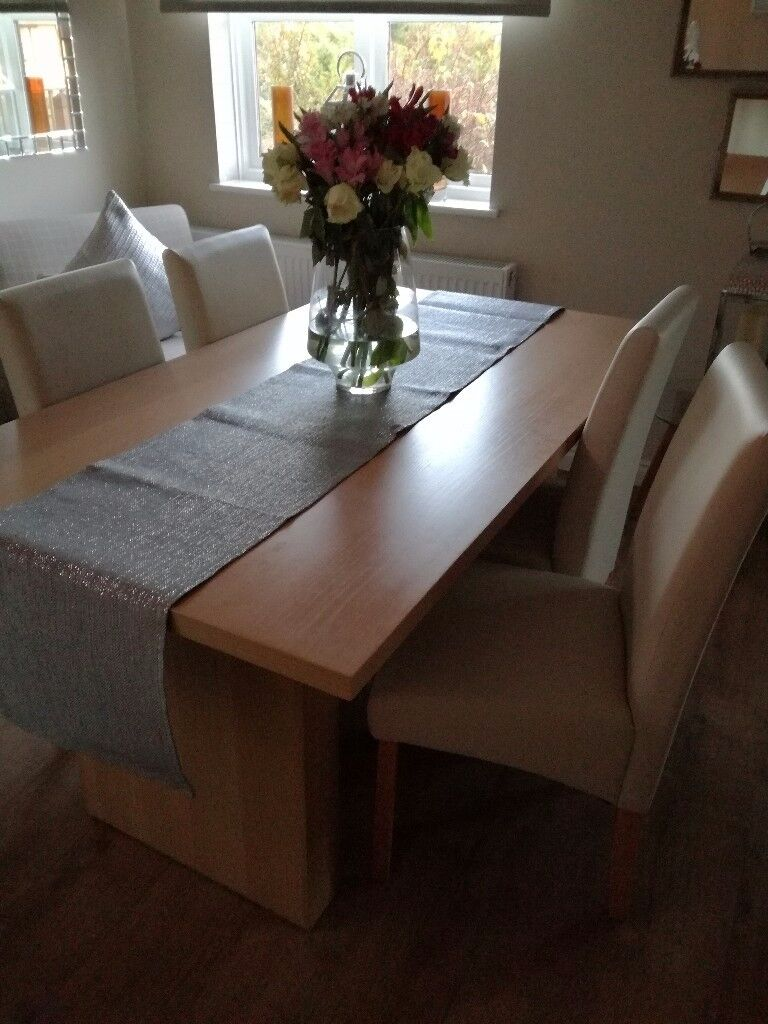 Beech dining table and 4 light cream leather effect chairs. Excellent condition..hardly used.