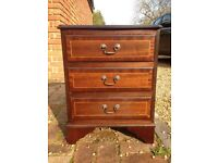 Dark wood bedside table with three draws