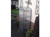 4 tier greenhouse with plastic cover that zips closed or door can be rolled up