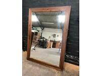 A giant modern wood framed mirror in pristine condition