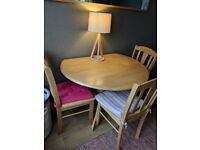 Dining table with drop sides and four chairs.