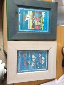 2 prints in frames of the sea and boats taken from a silk painting