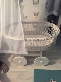 White wicker Moses basket on wheels