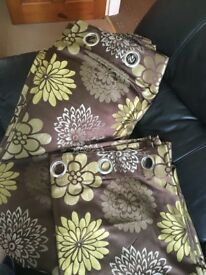 Brown and green flowered curtains, cushions, throw and lamp shade