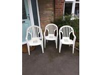 3 plastic white chairs
