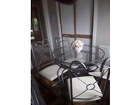 Metal and glass dining table with 4 chairs covered in beige material