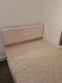 Cream fabric double bed with two drawers.