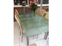 Extending glass dining table with 6 faux leather cream chairs.