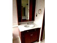 Bathroom vanity unit with marble top, sink, taps and mirror