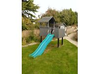 Children's wooden play house on stilts, with slide
