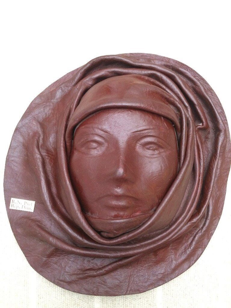 Real leather sculptured face wall hanging.