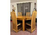 Large circular dining table with six solid chairs
