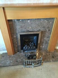 gas fire with marble surrounding and wooden frame.