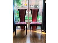 A pair of fabulous colourful dining room chairs.