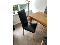 Solid wood dining table with black chairs