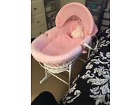 White wicker Moses basket with pink bedding